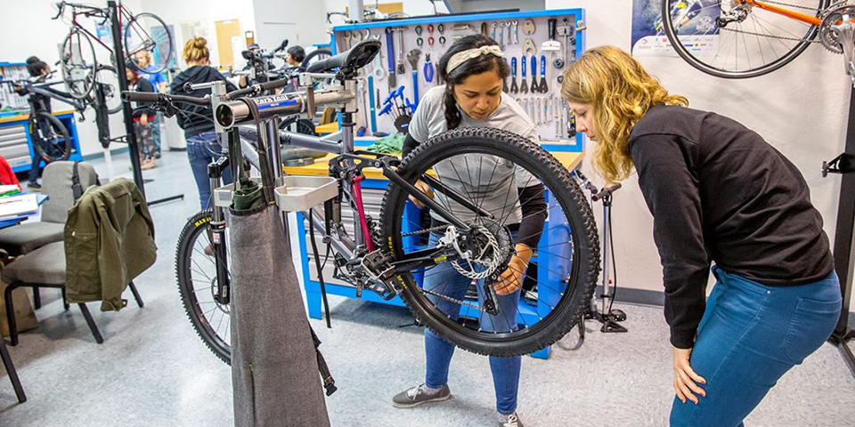 Elyse Bejasa and Lee James work on a rear derailleur.