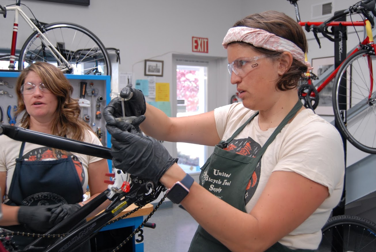 Jessica finishes up a SRAM Brake Bleed during class, with her partner Acacia Wytaske, who happend to be wearing the same Swift Industries shirt that day.