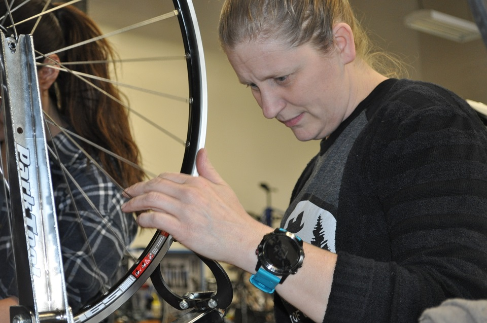 Wyman focuses on getting her wheel true during the second day of the QBP Bike Mechanic Scholarship at UBI Portland.
