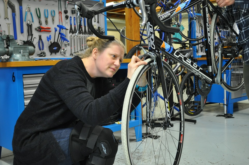 Wyman finishes up her front brake adjustment during Day 9, the bicycle overhaul!