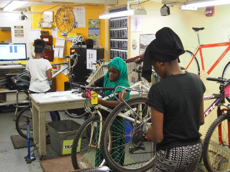 Young women learning all about how bicycles work and how to fix them in the Old Spokes Home.